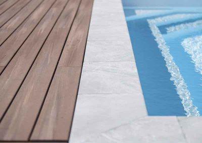 Terrasse en lames composites et margelles en pierre naturelle